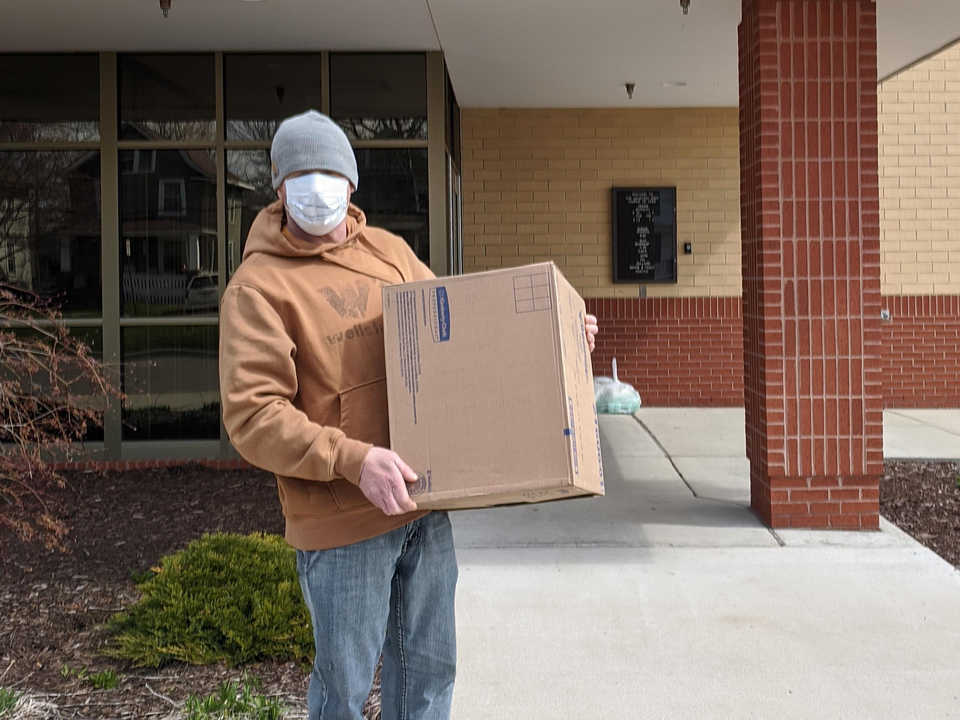 Worker with face mask carrying a box outside of Salvation Army