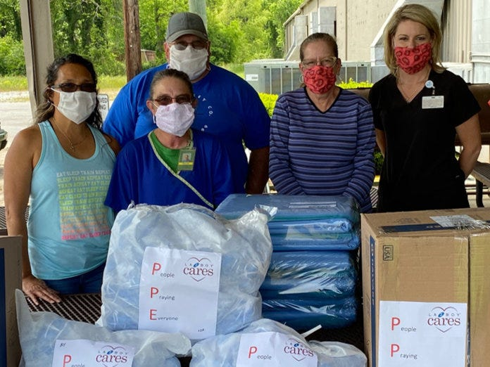 Workers behind bags and boxes of personal protective equipment